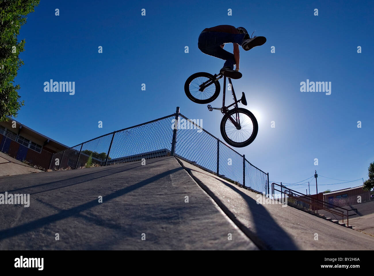 A mountain bike rider does a tailwhip on a concrete bank in Albuquerque, NM. - Stock Image
