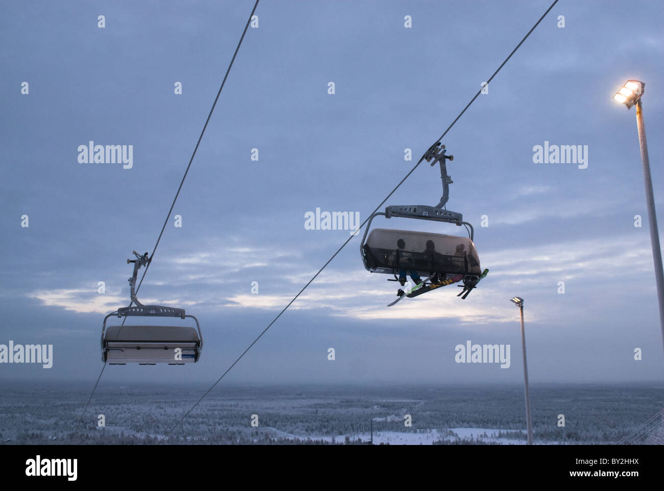 Skiers on the chair ski-lift of Pyhätunturi, Lapland, Finland photographed during the mid-winter 'blue - Stock Image