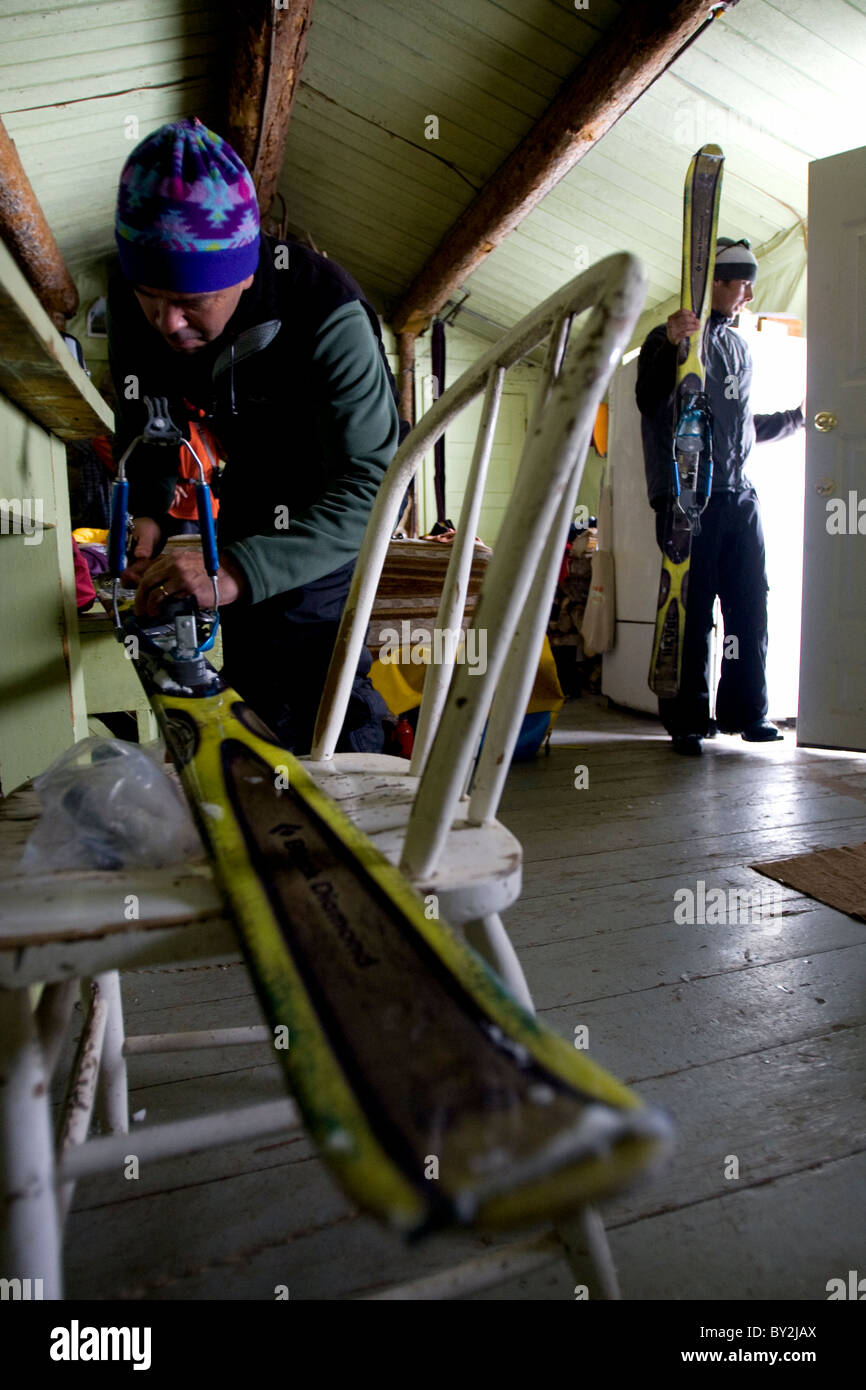 Two male skiers fixing skis and walking out the door of a rustic backcountry cabin. - Stock Image