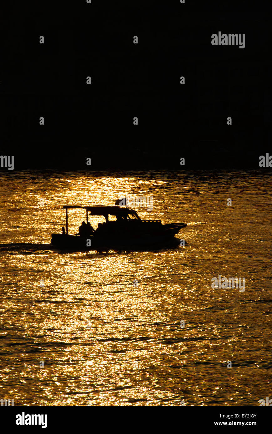 A small fishing boat is silhouetted against the glistening water of the Bosphorus during a golden sunset in Istanbul, - Stock Image