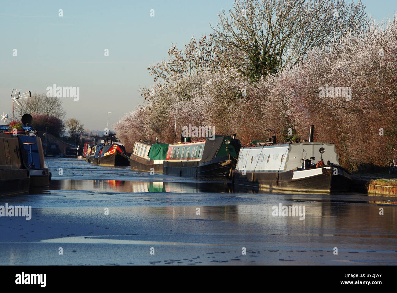 Narrowboats in the ice on The Grand Union Canal at Blisworth Arm, Northamptonshire, UK - Stock Image