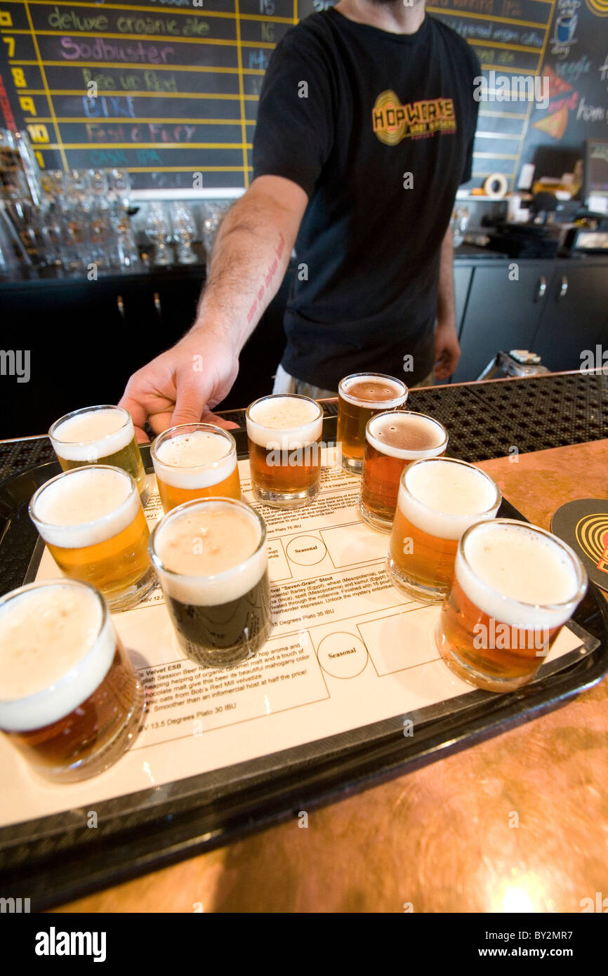 Man serves selection of craft beers. - Stock Image