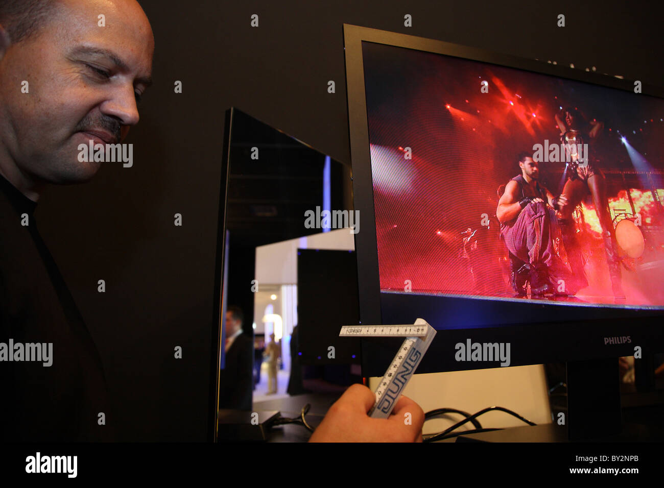 IFA 2008, a man measuring the width of an LCD screen, Berlin, Germany Stock Photo