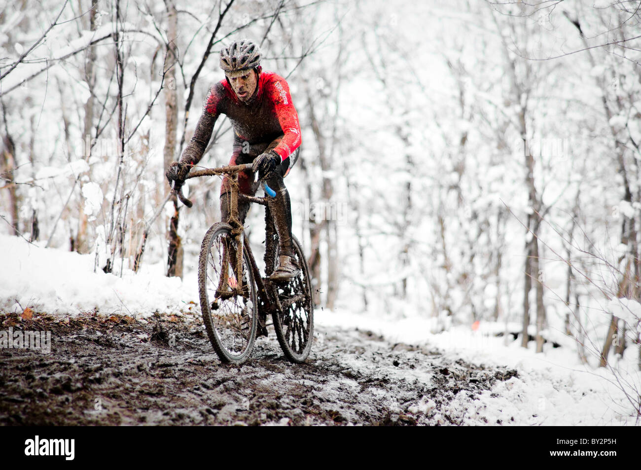 A cyclists races in the mud and snow at a Cyclocross race in Boulder, CO. Stock Photo