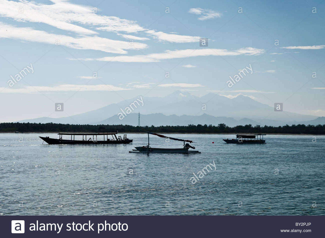 Anchored boats with Gunung Rinjani in the distance, Gili Trawangan, Indonesia. - Stock Image
