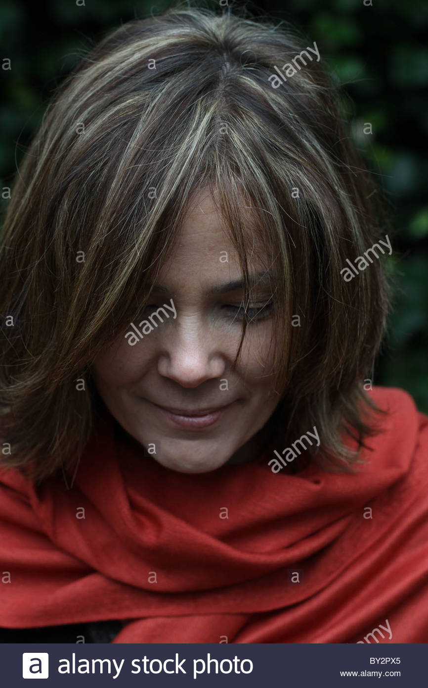 A close up of the face of a woman in her forties with head bowed, eyes closed, and smiling - Stock Image