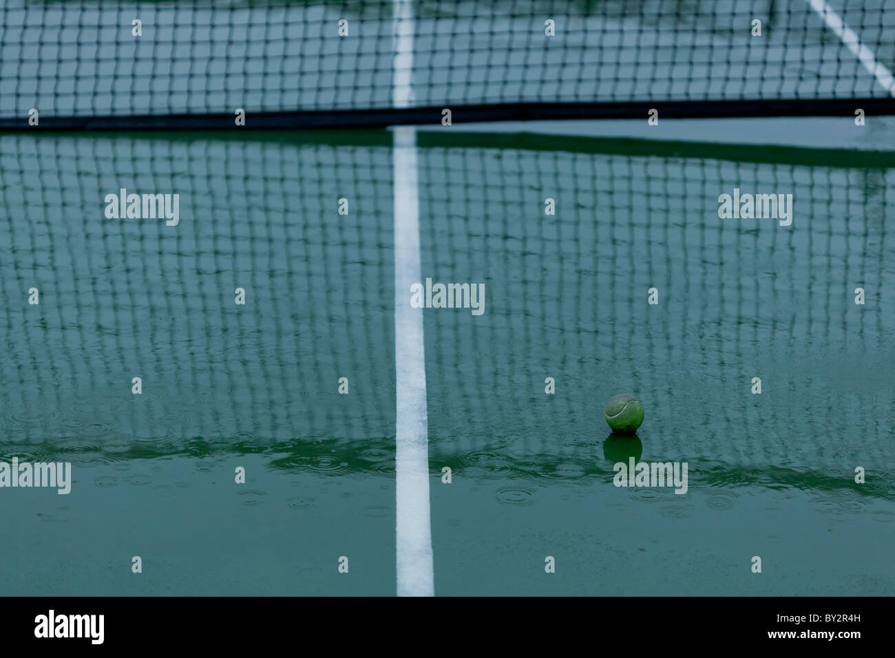 Home tennis ball on the court during a rainy day. - Stock Image