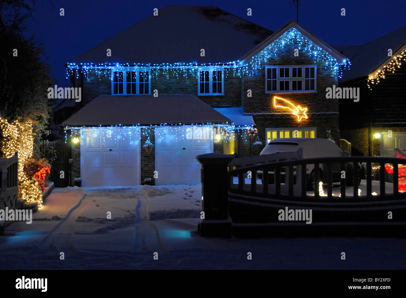 Snow house and garage driveway with Christmas lights - Stock Image