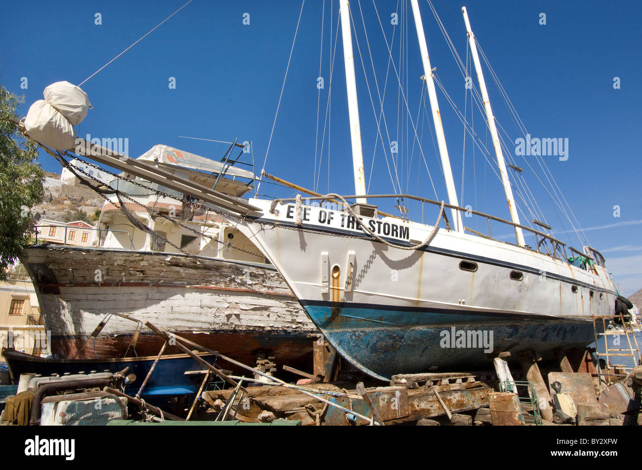 A pair of old Greek pleasure boats 'Eye of the Storm' and 'Lazy Days' in a boatyard on the Greek - Stock Image