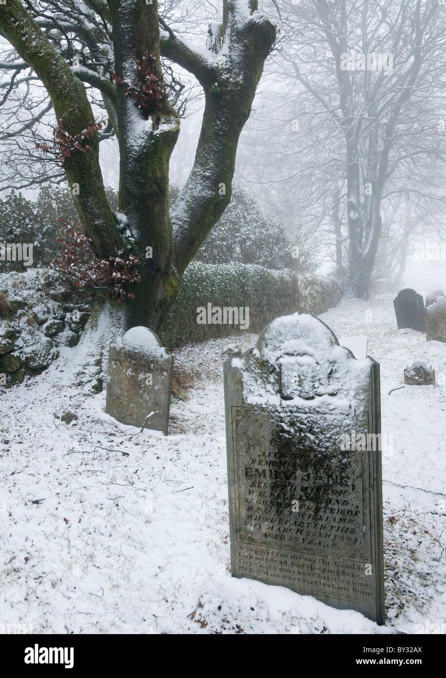 Headstones in Princetown church covered in snow, Dartmoor, Devon UK - Stock Image