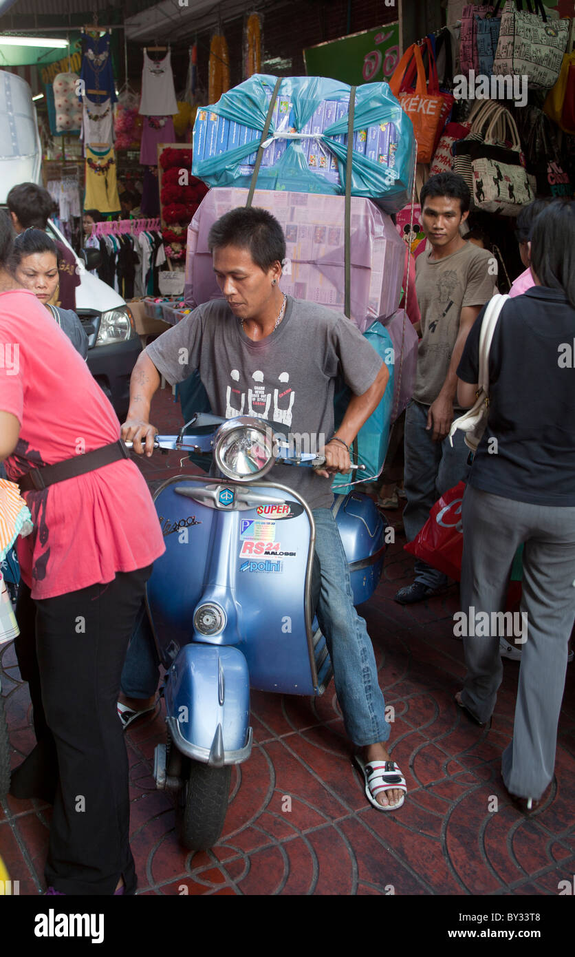 Courier Rider on classic Vespa scooter carrying sacks of