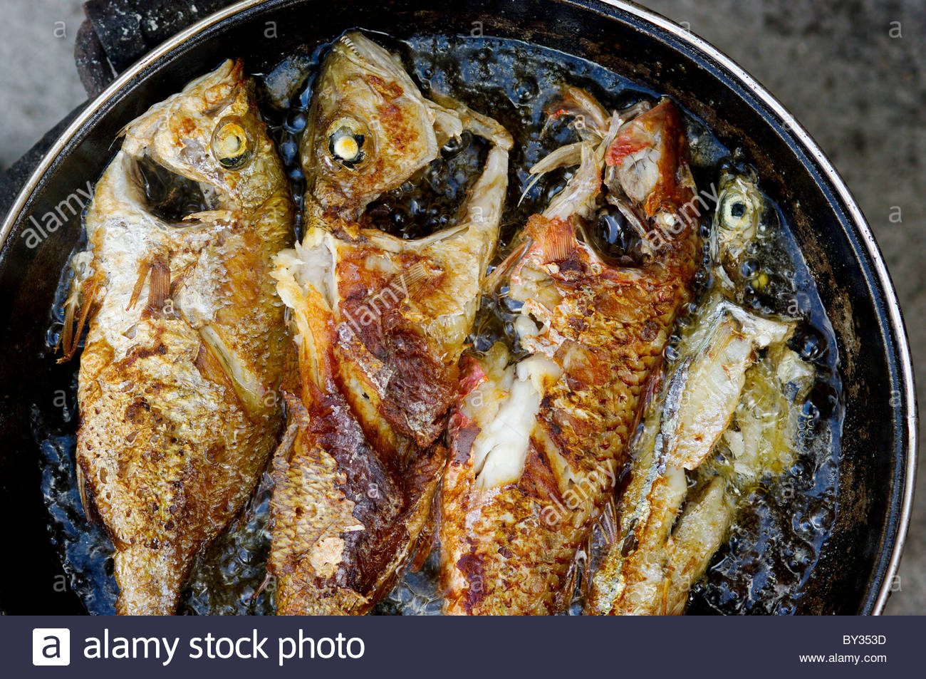 Fried fish frying in a pan filled with cooking oil for Oil for frying fish
