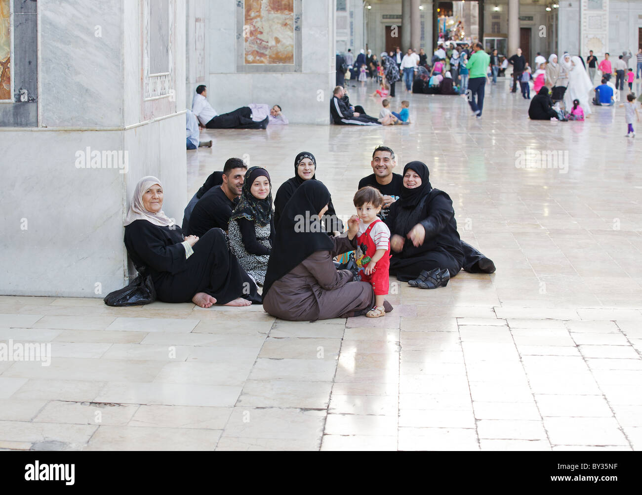Syrian family relaxing in Great Umayyad Mosque, Damascus, Syria - Stock Image