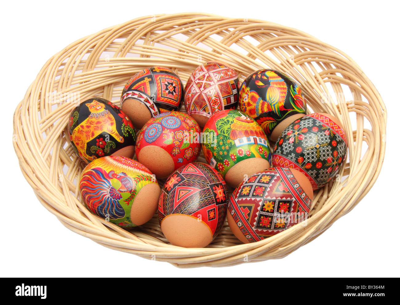 Basket with multicolored easter eggs on the white background - Stock Image