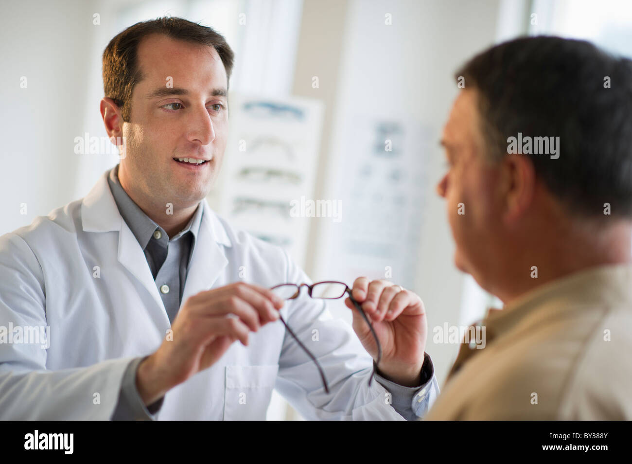 USA, New Jersey, Jersey City, Optician showing man glasses in shop - Stock Image