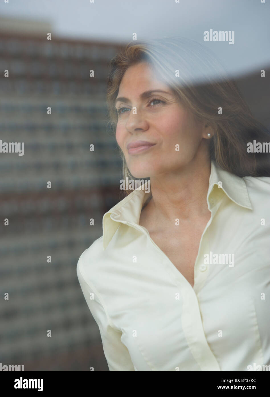 USA, New Jersey, Jersey City, Businesswoman looking through window - Stock Image