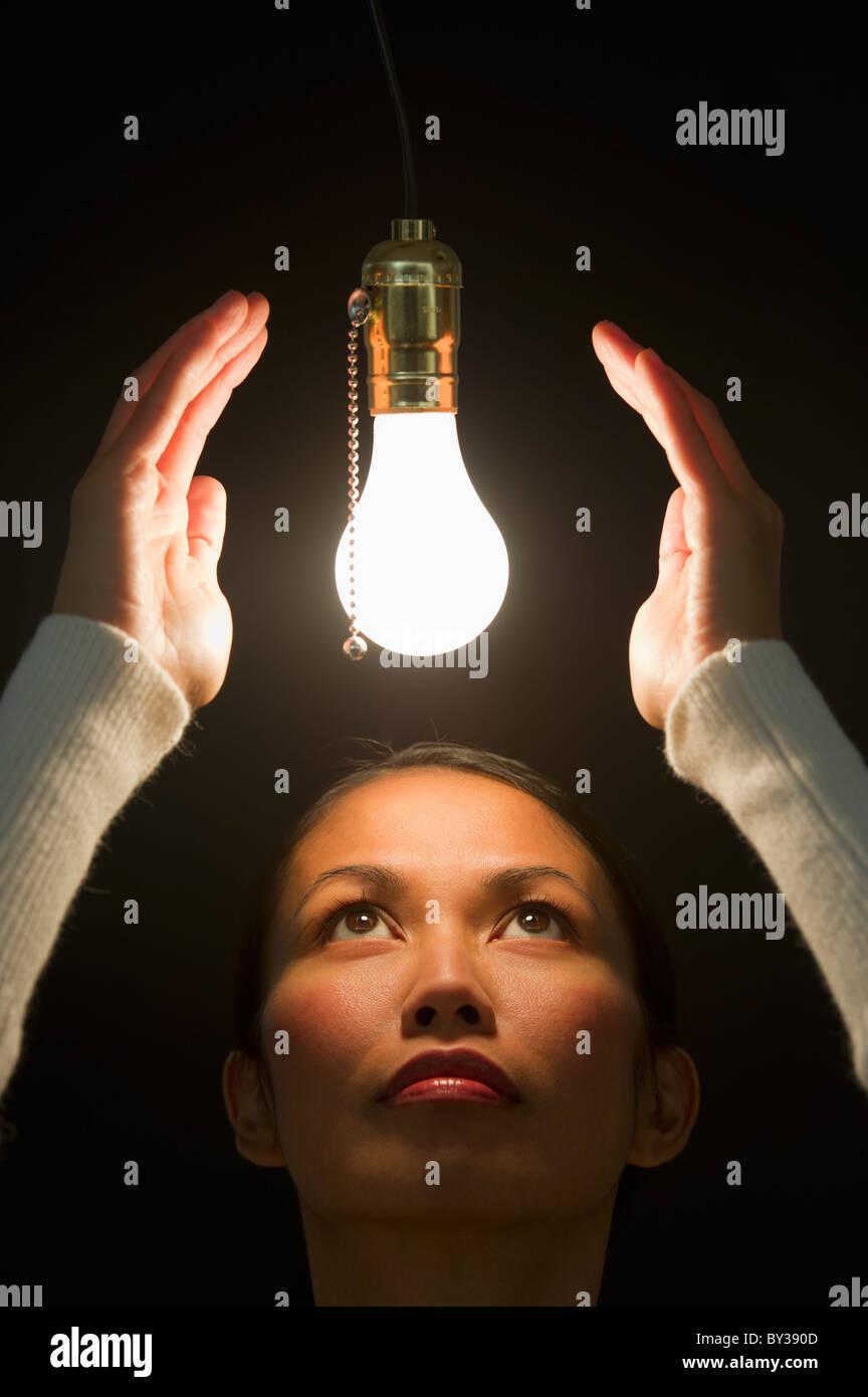 Woman looking up at illuminated lightbulb - Stock Image
