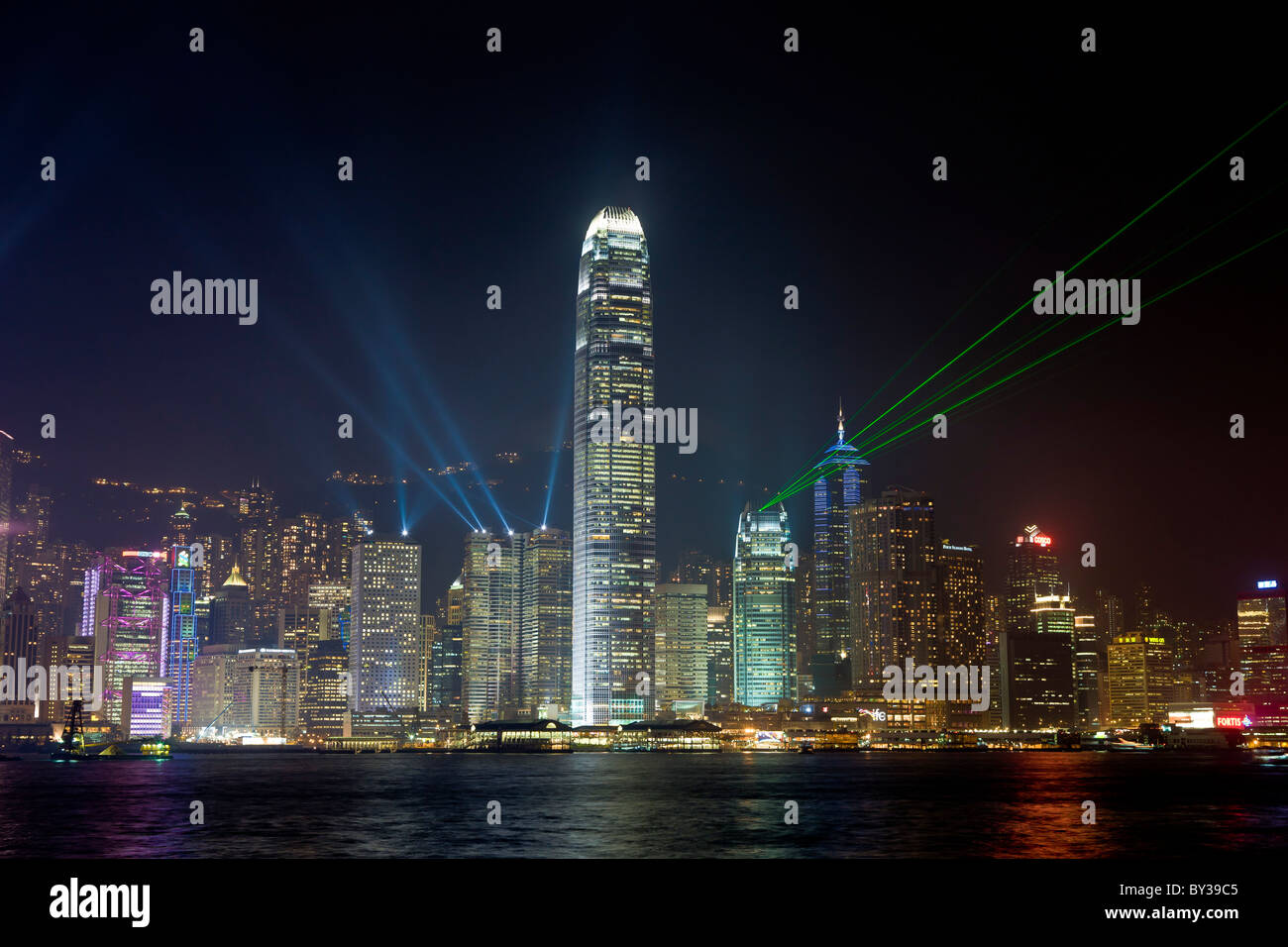 Laser light show Hong Kong Island at night viewed across Victoria Harbour from Kowloon. JMH4154 - Stock Image