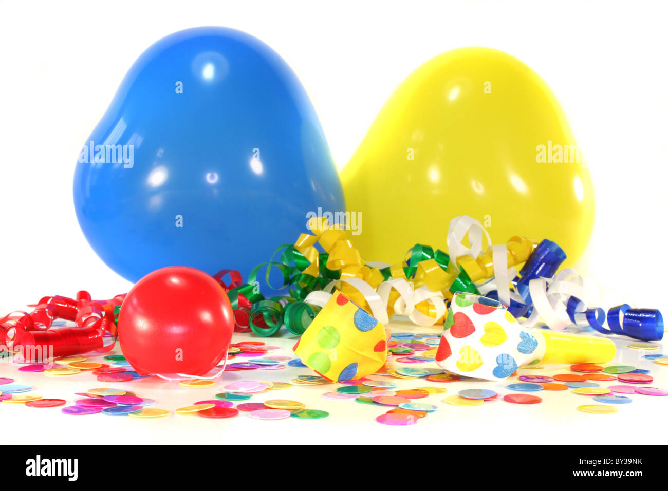 Noisemaker with a red clown nose, colorful confetti, heart balloons and streamers - Stock Image