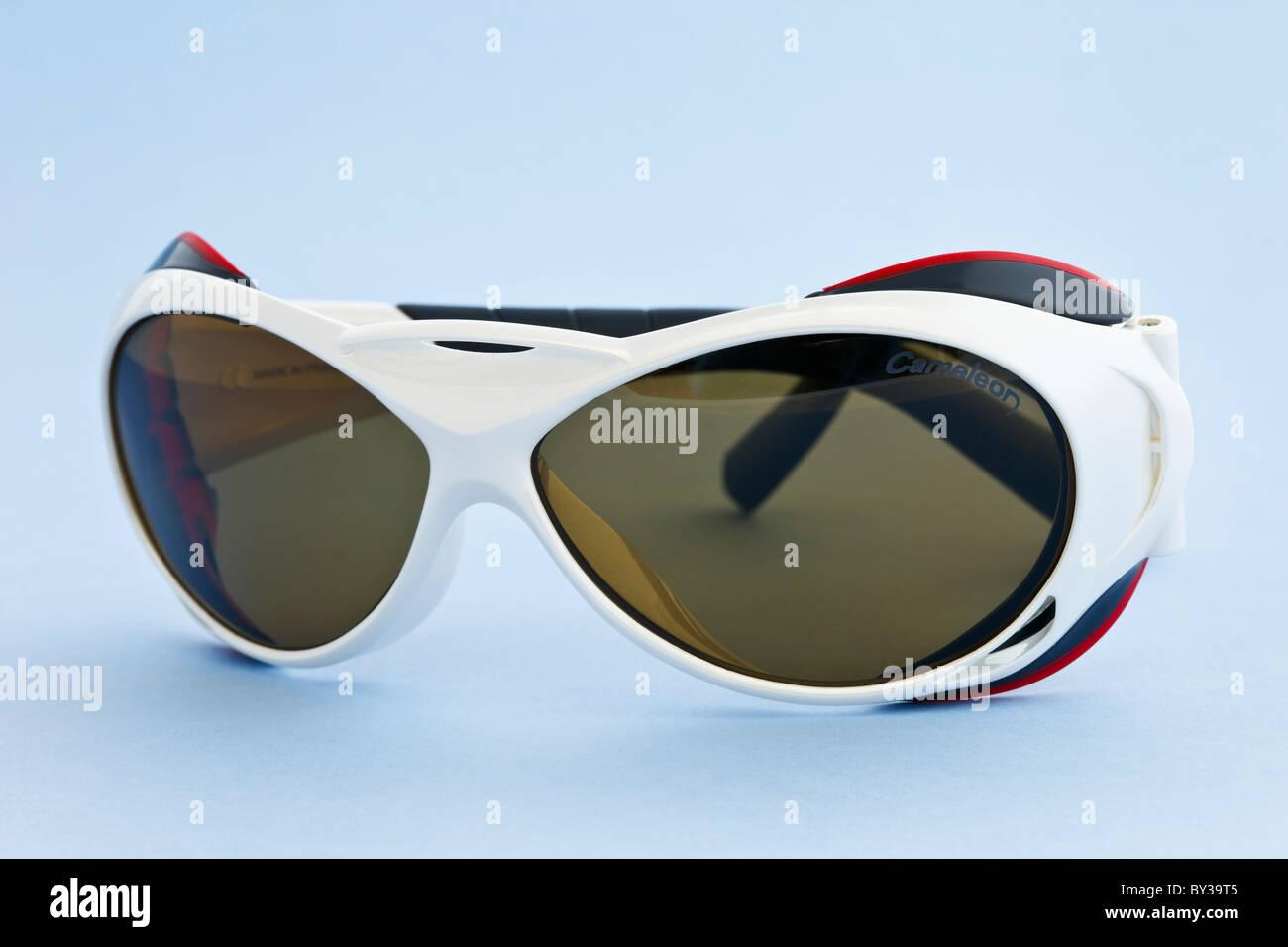 6255cdcc586 Julbo Explorer glacier sunglasses with Cameleon photochromic dark lenses on  a blue background