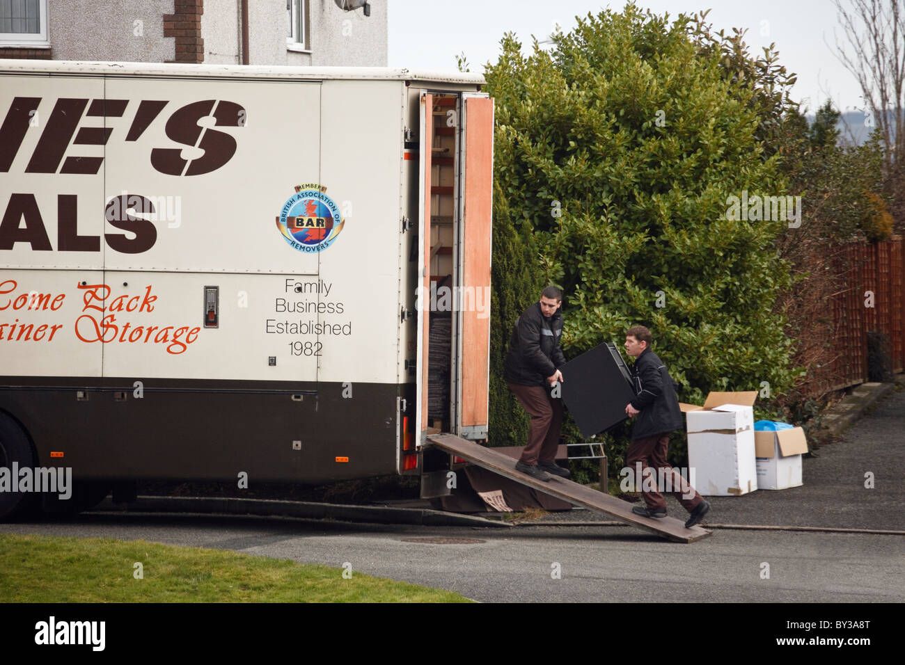 North Wales, UK, Europe. Men carrying furniture into a removal van in the street outside a house for home removals Stock Photo