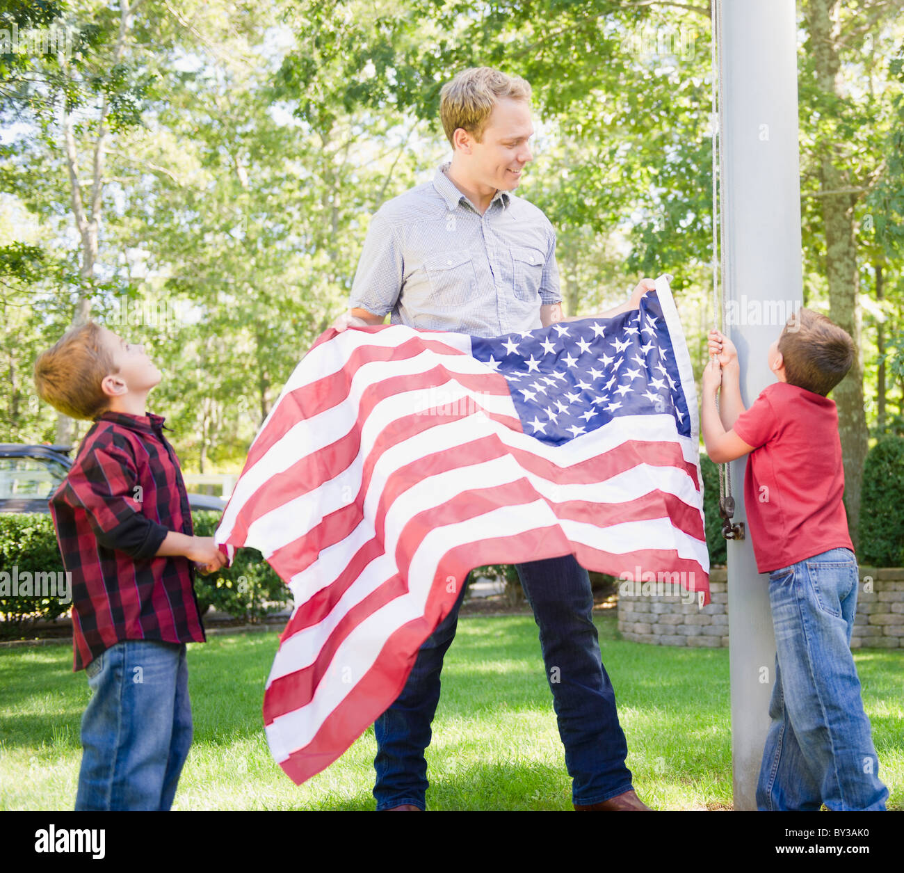 USA, New York, Flanders, Father with two boys (4-5, 8-9) hanging American flag on pole - Stock Image
