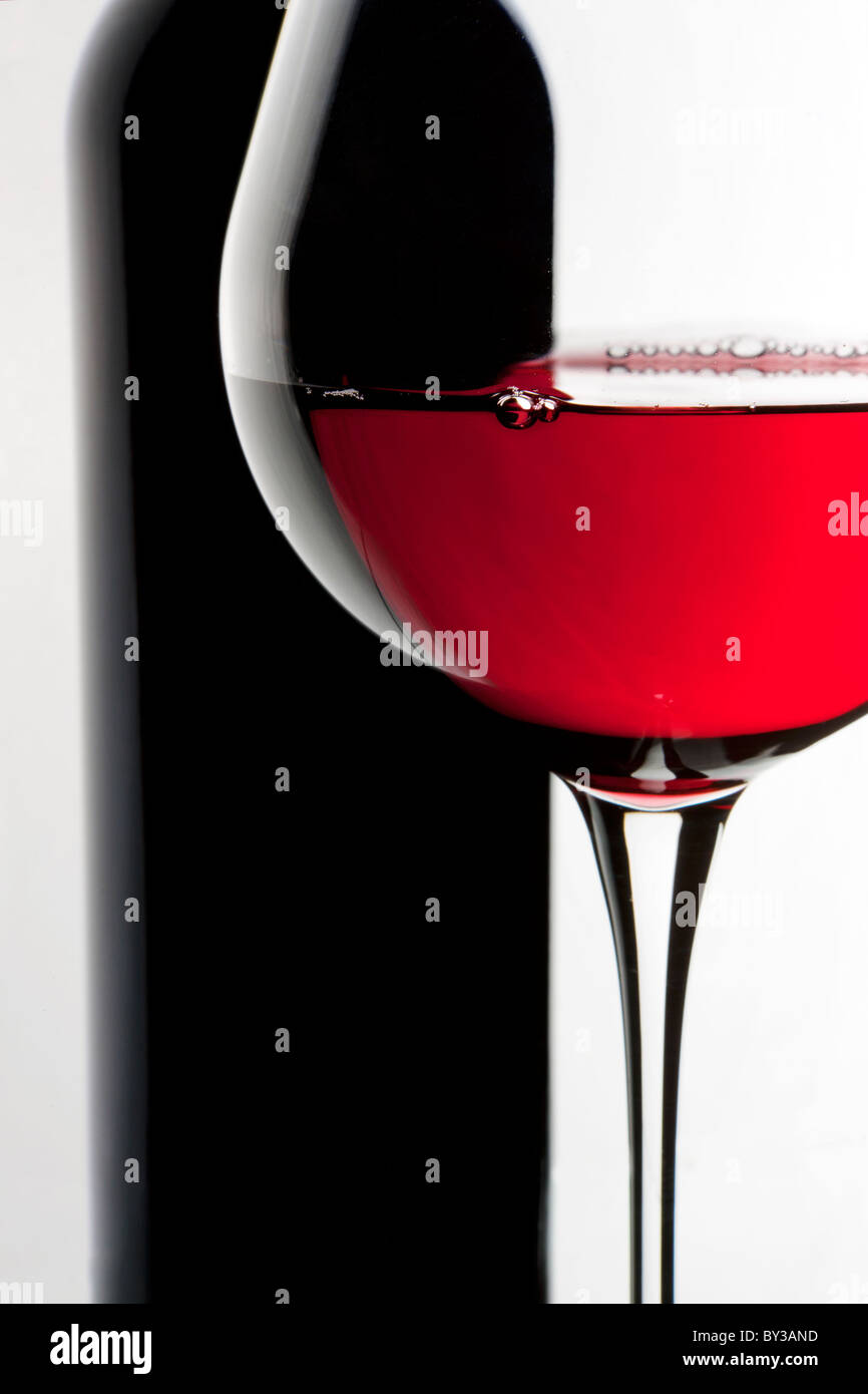 Still-life with bottle and glass of red wine over white background. - Stock Image