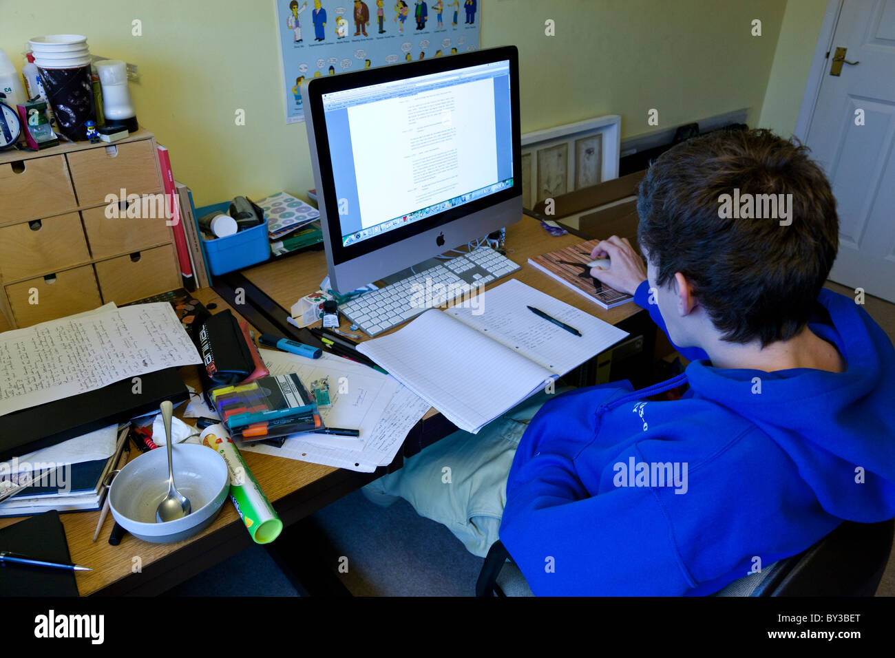 Student Working In His Bedroom With A Messy Desk And An Imac.