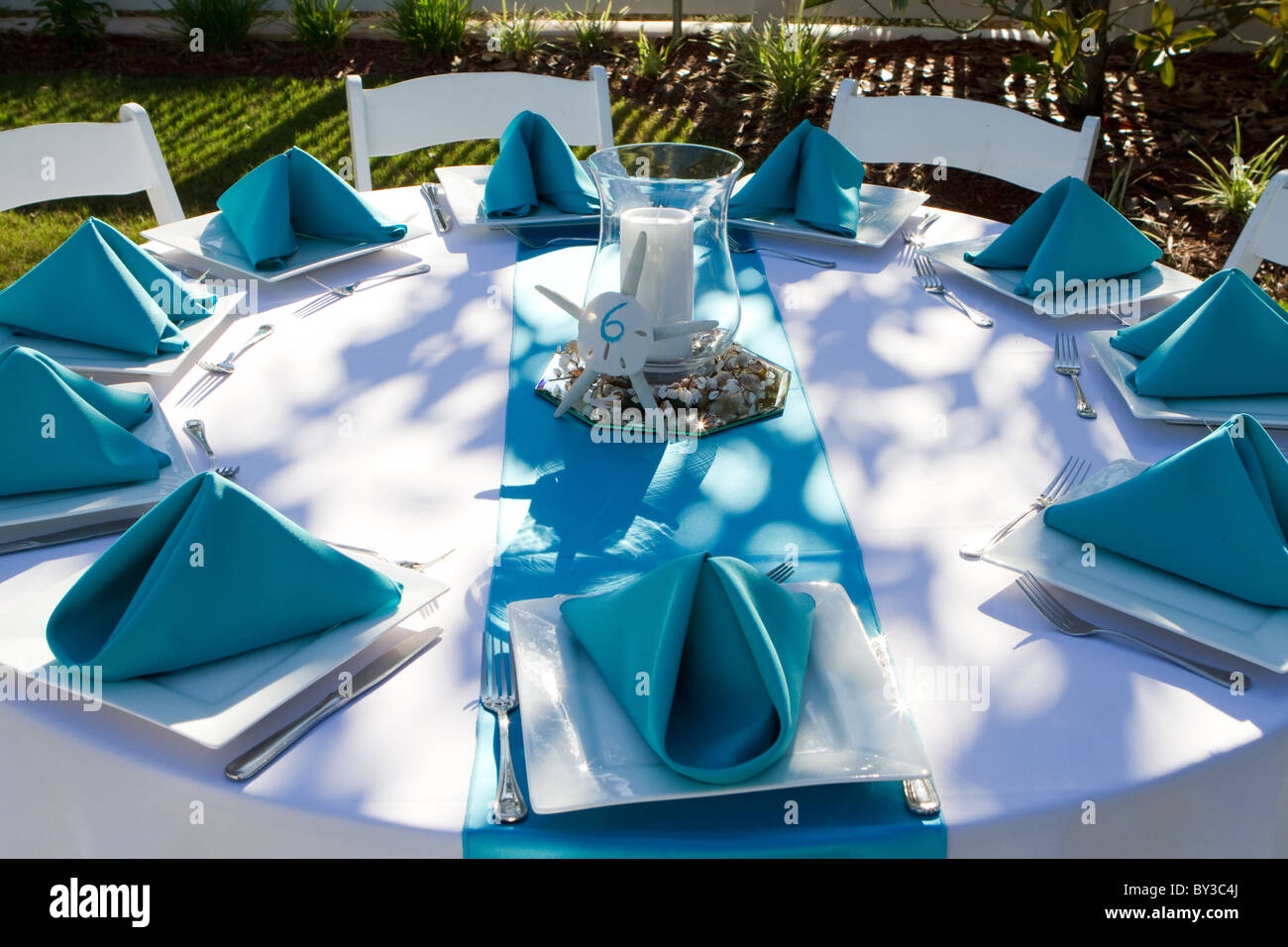 Outdoor dinner table is setup with plate, silverware and folded ...