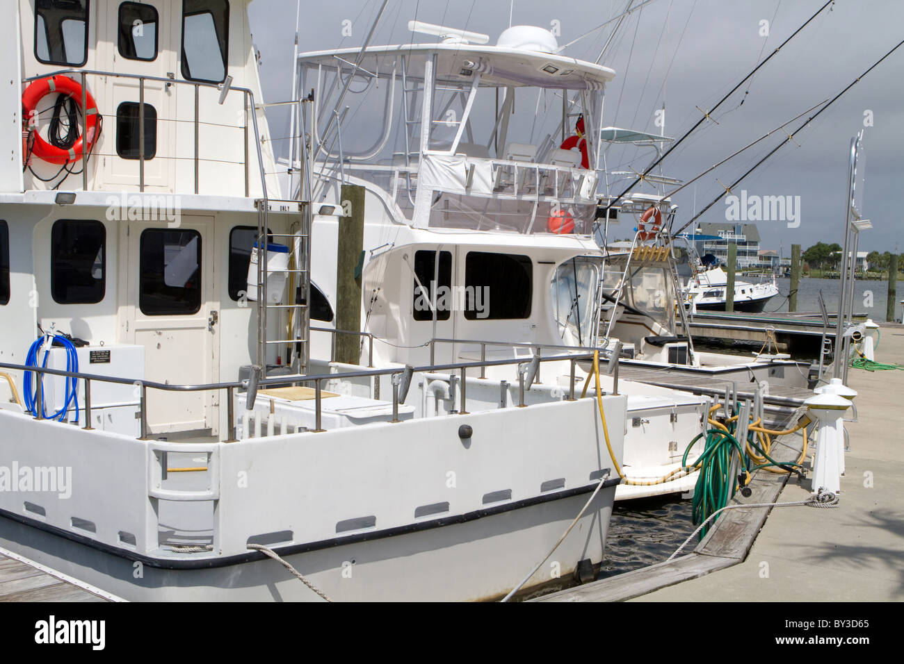 Charter fishing boats sit idle at the dock. - Stock Image