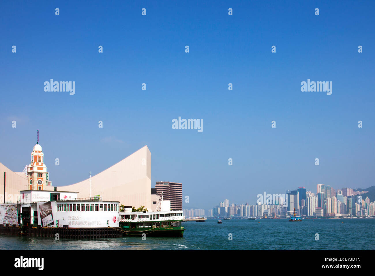 The Star Ferry, moored at Kowloon with Hong Kong island in background across Victoria Harbour harbor buildings modern - Stock Image