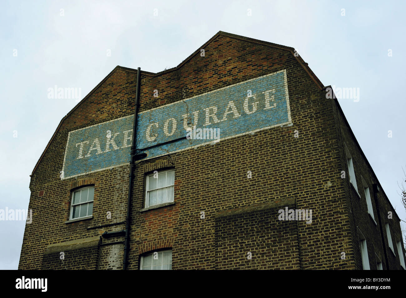 Take Courage Advert on What used to be The Courage & Co. Ltd Brewery - Stock Image