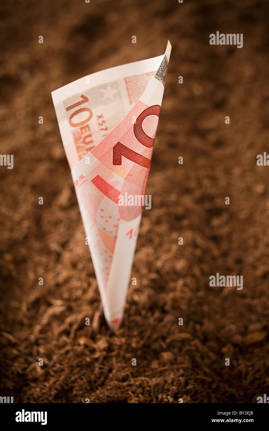 Ten euros Banknote growing from dirt, studio shot - Stock Image