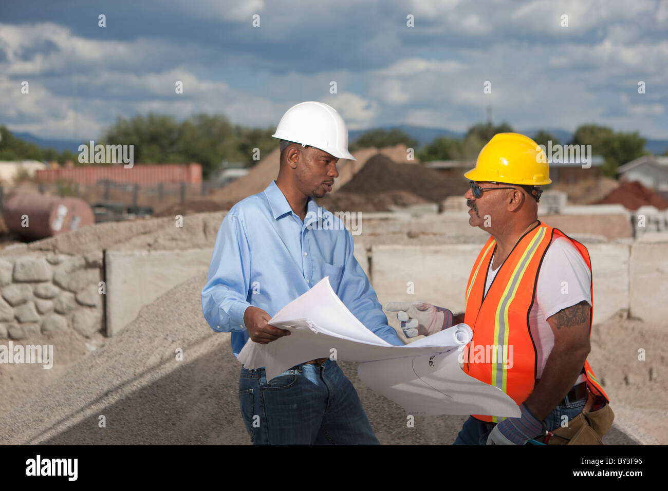 African american construction workers outdoors stock photos two construction workers discussing blueprints on building site stock image malvernweather Images