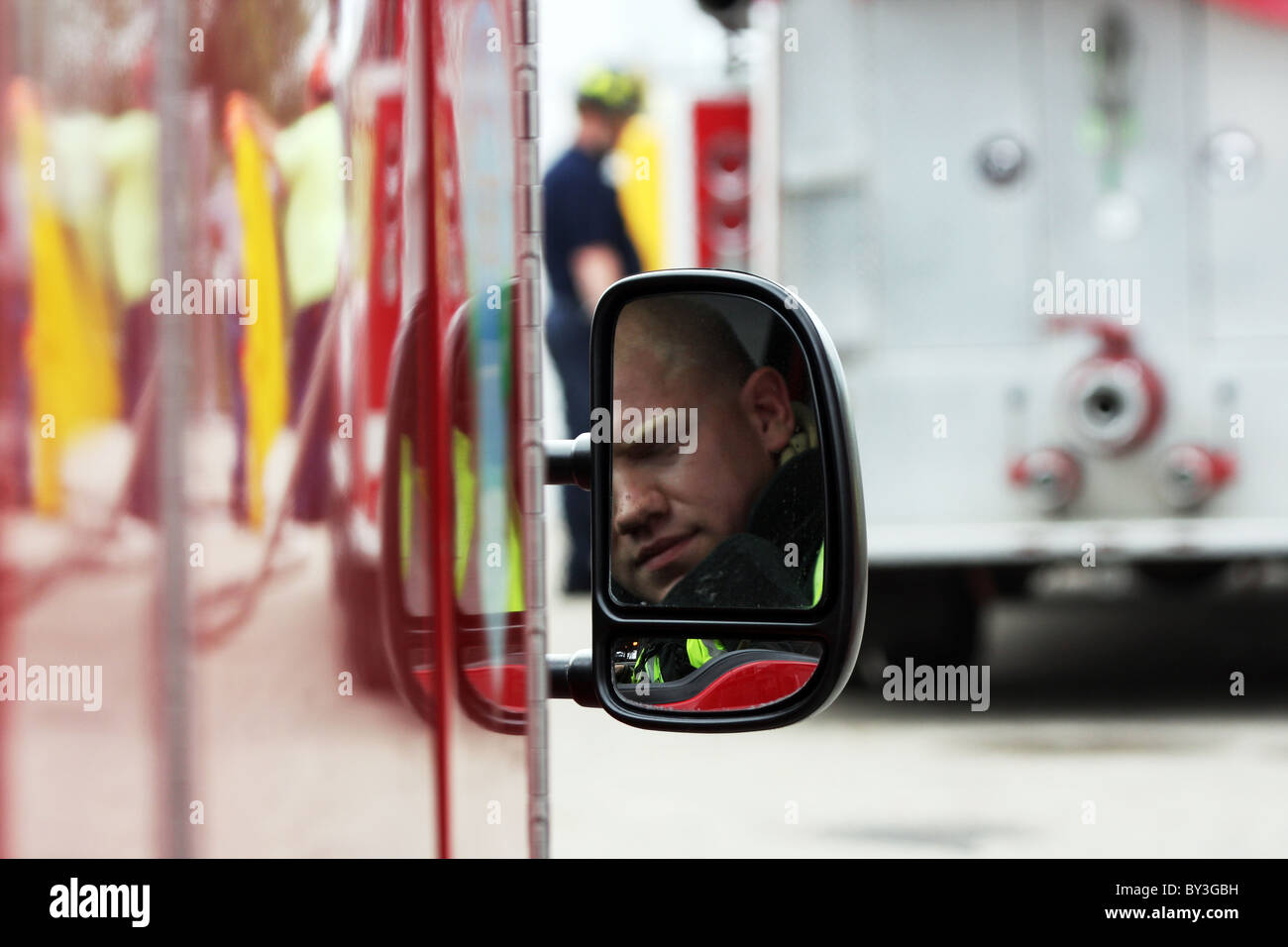 A firefighter reflection in the fire truck vehicle rear view side mirror and a firefighter in the background Stock Photo