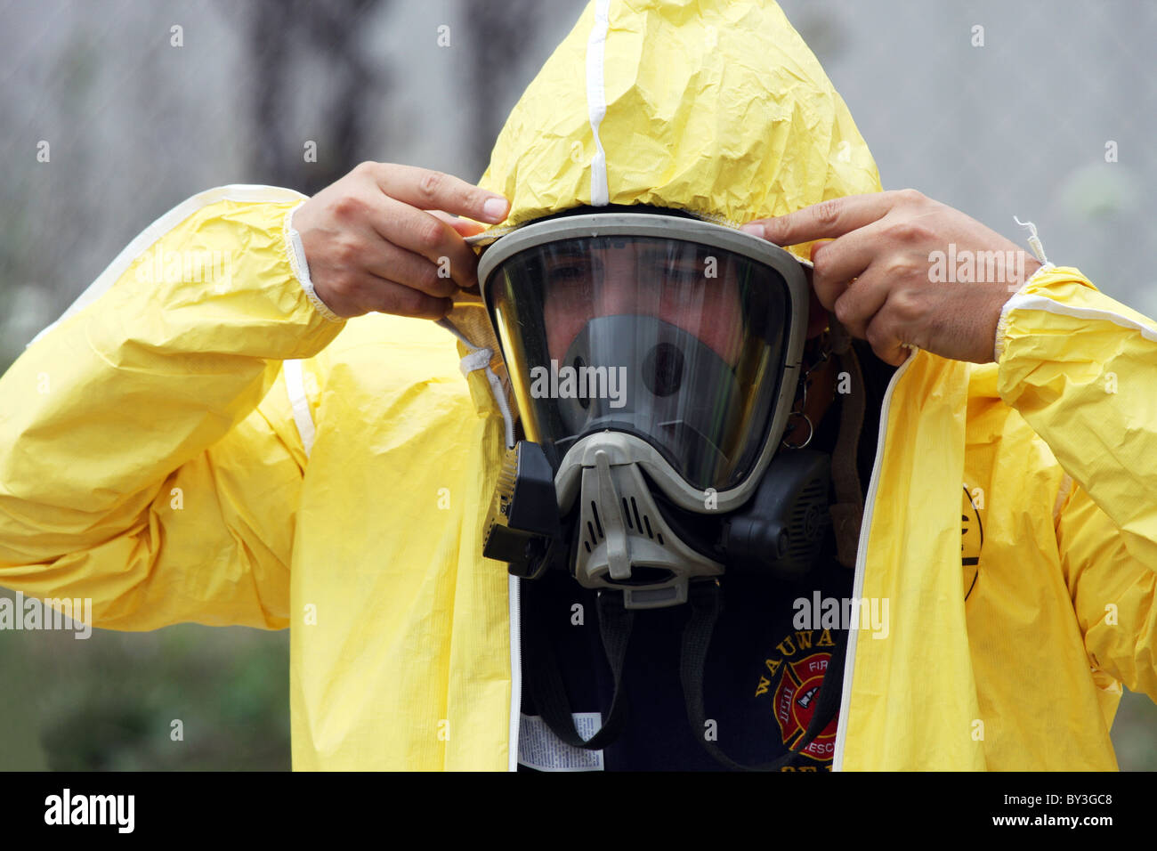 A firefighter putting on a yellow body suit protector for a hazmat situation - Stock Image