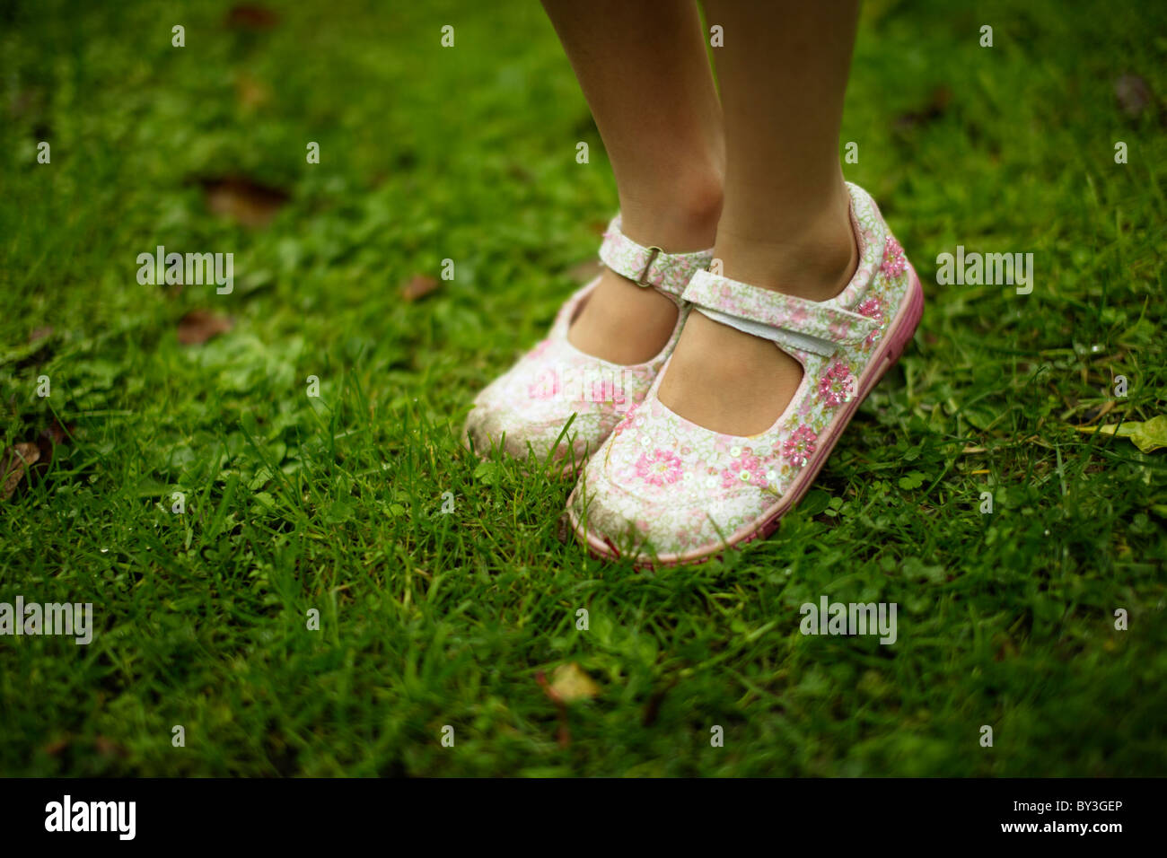 Girl's glittery shoes on lawn - Stock Image