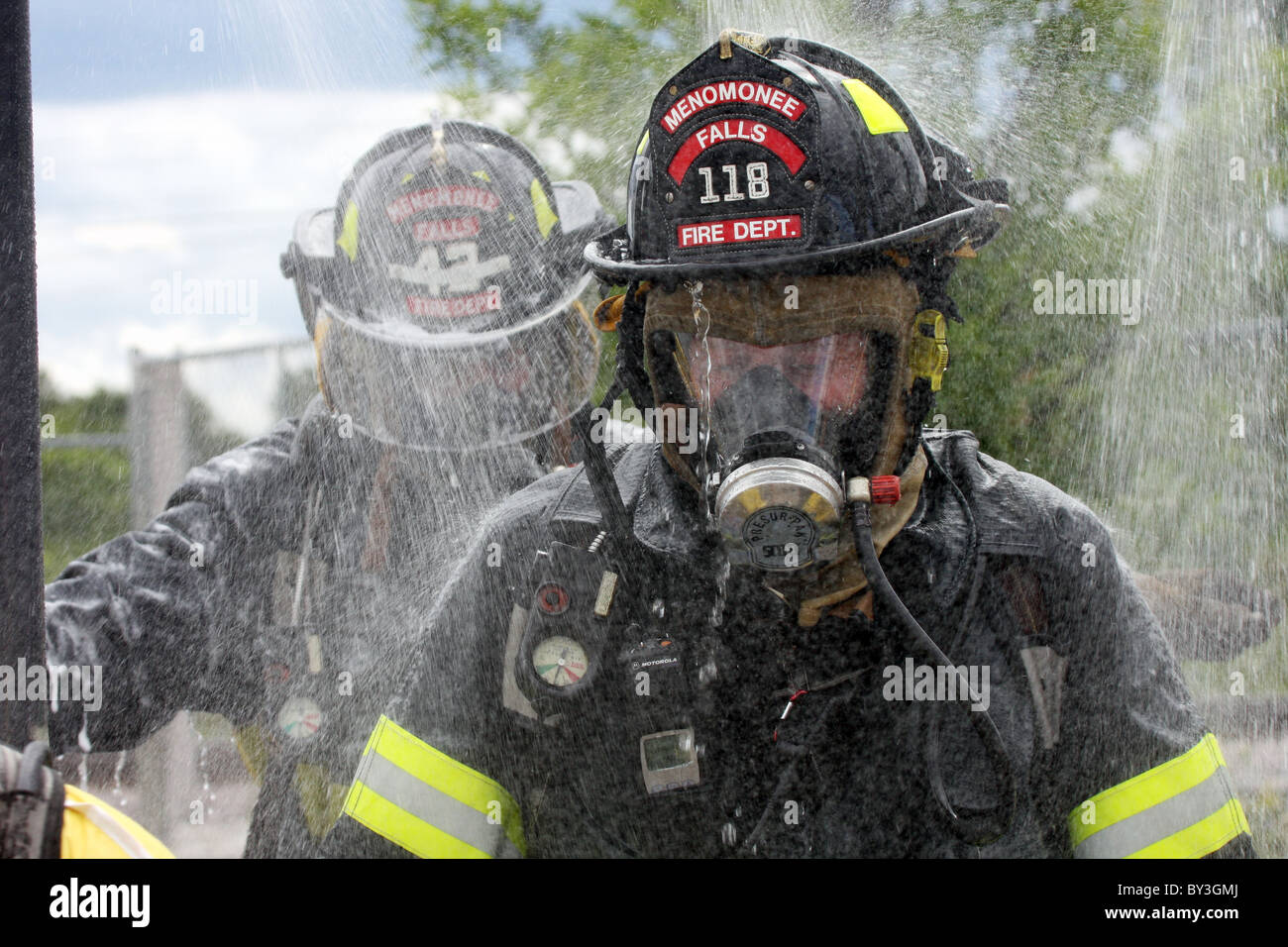A firefighter getting sprayed down after a chemical haz mat spill incident - Stock Image