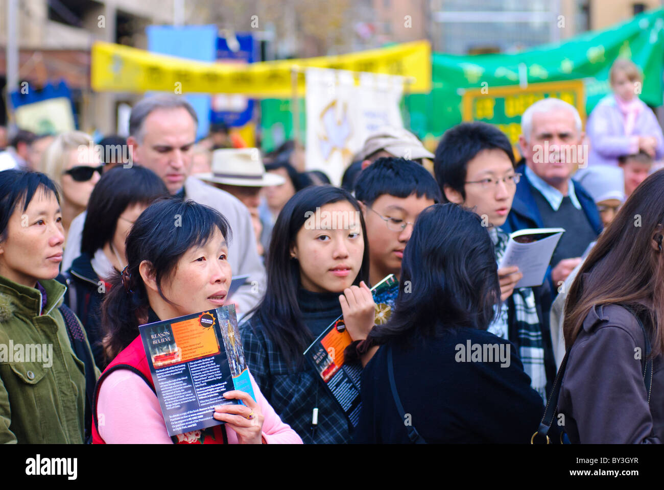 Catholic procession through city streets. Migrants from many cultures are among the people participating. - Stock Image