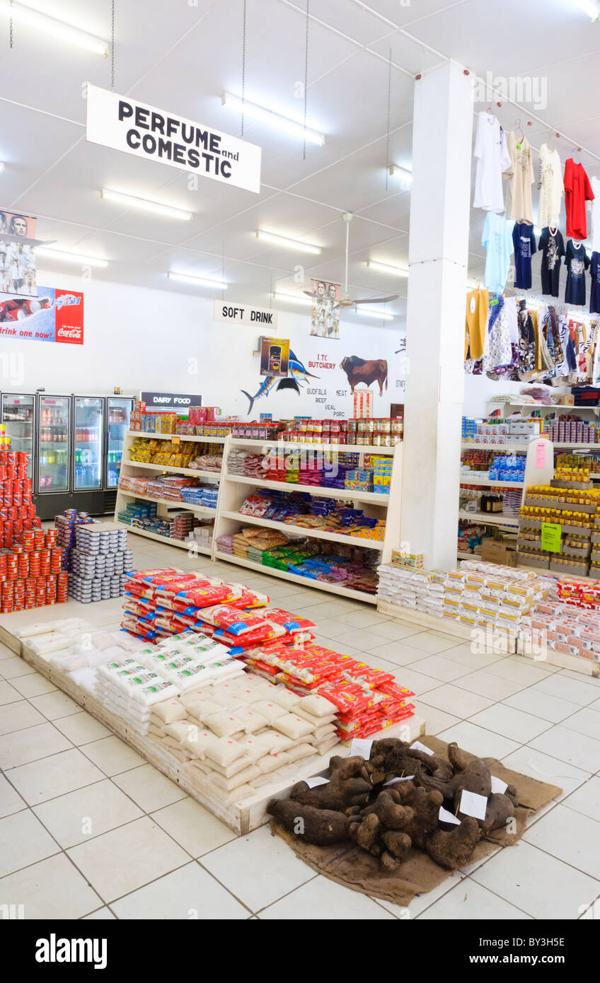 Interior of a supermarket in a developing country, with rice and root vegetables on the floor. - Stock Image