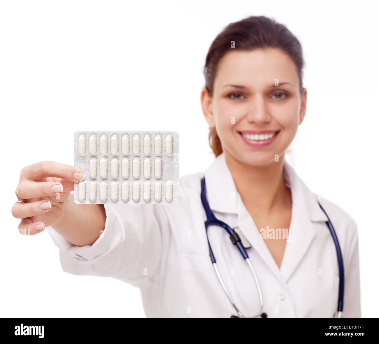 Doctor giving a pill. Hand with pills is front plan. - Stock Image