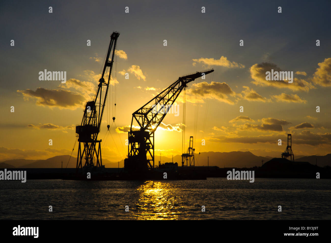 Sunset view (landscape / seascape) of derrick cranes on wharves at an industrial port in Asia - Stock Image