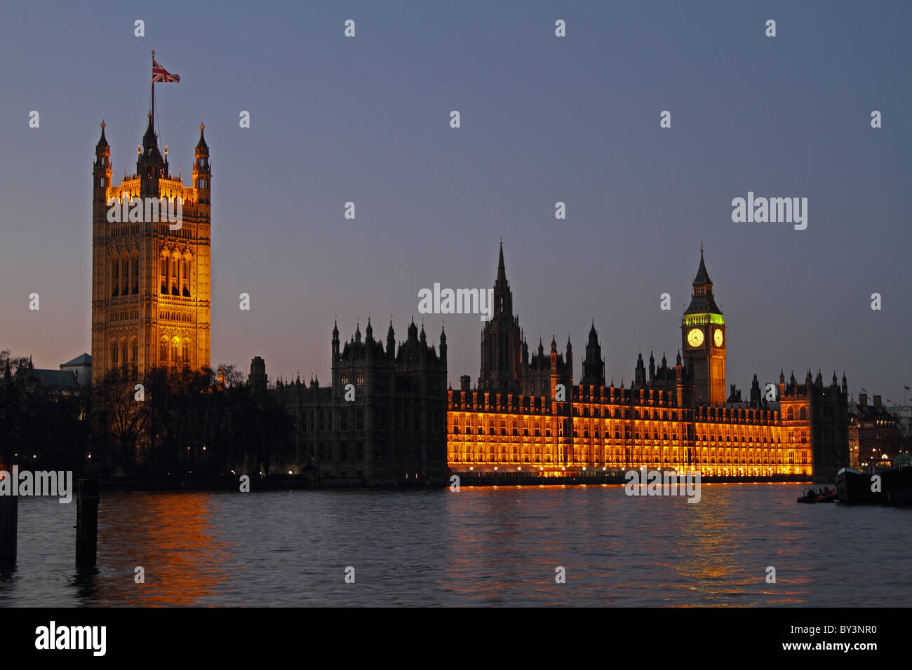 Houses of Parliament night night evening floodlit London Westminster Thames - Stock Image