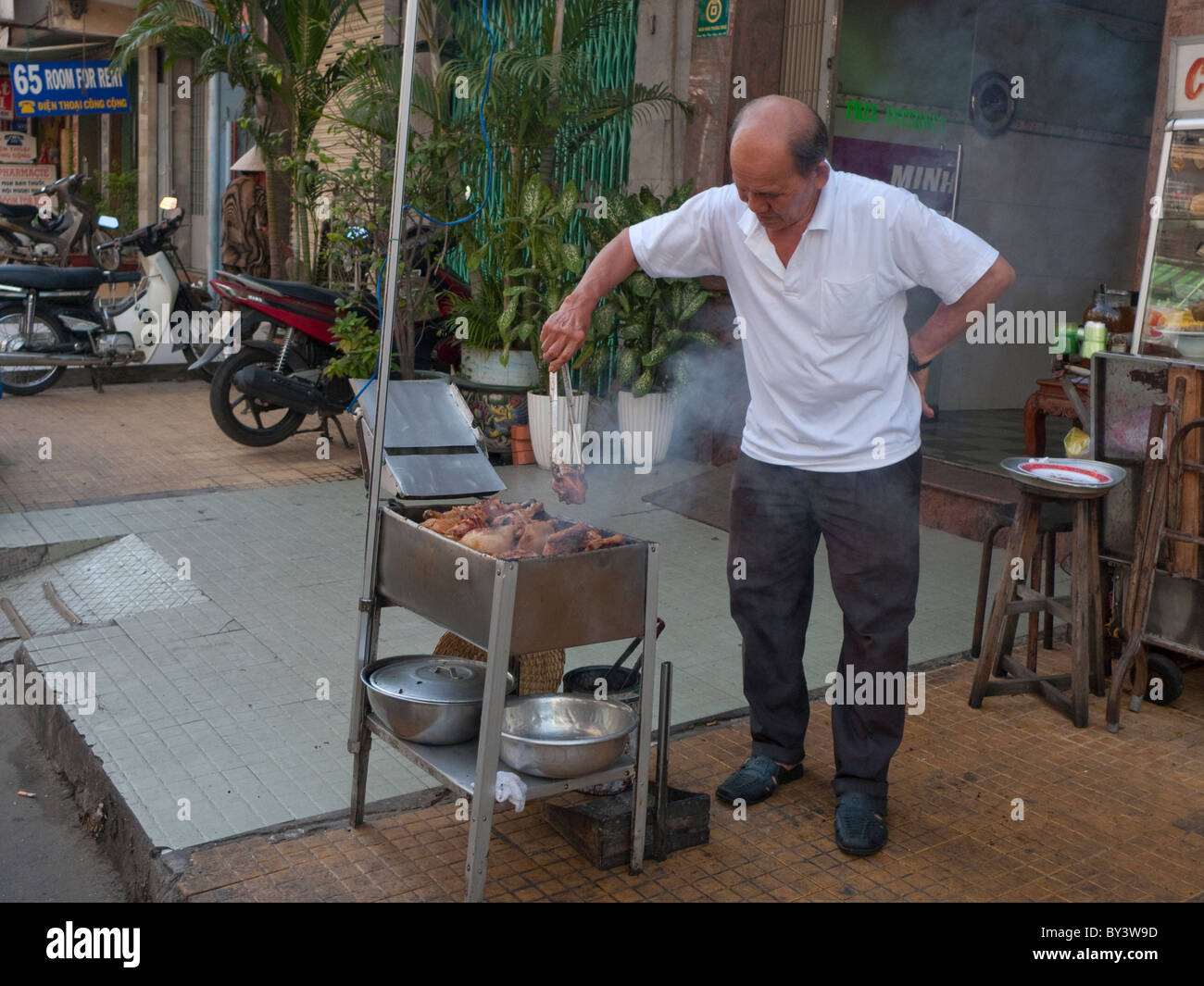 A food vendor sits cooking fried bananas for sale on a street in Ho Chi Minh, Vietnam - Stock Image