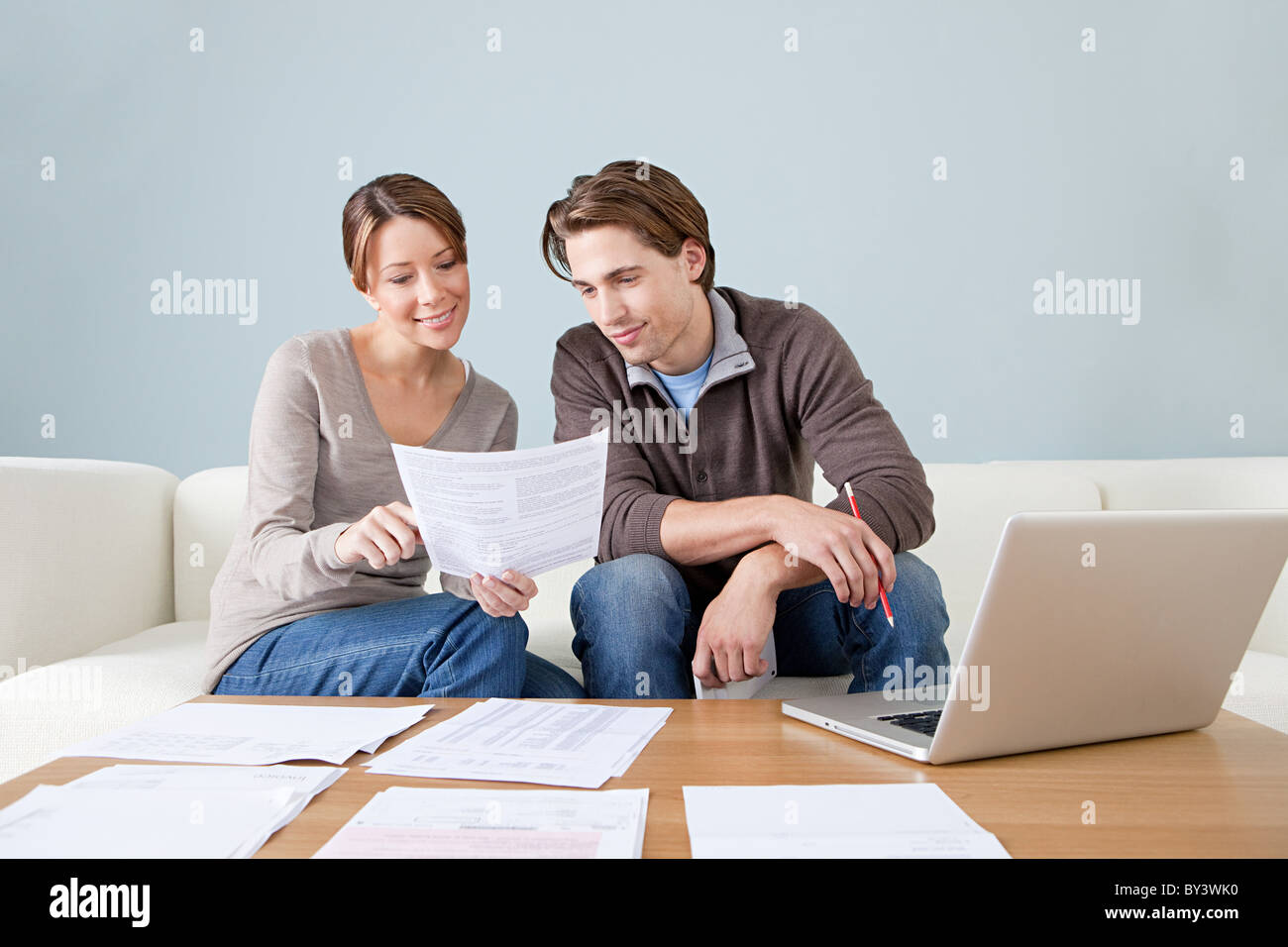 Young couple using computer and doing paperwork - Stock Image