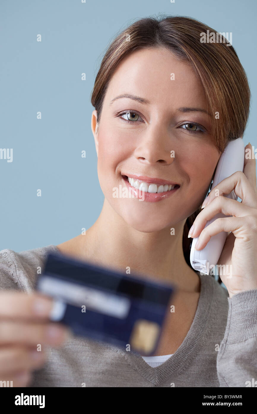 Young woman on the phone with credit card - Stock Image