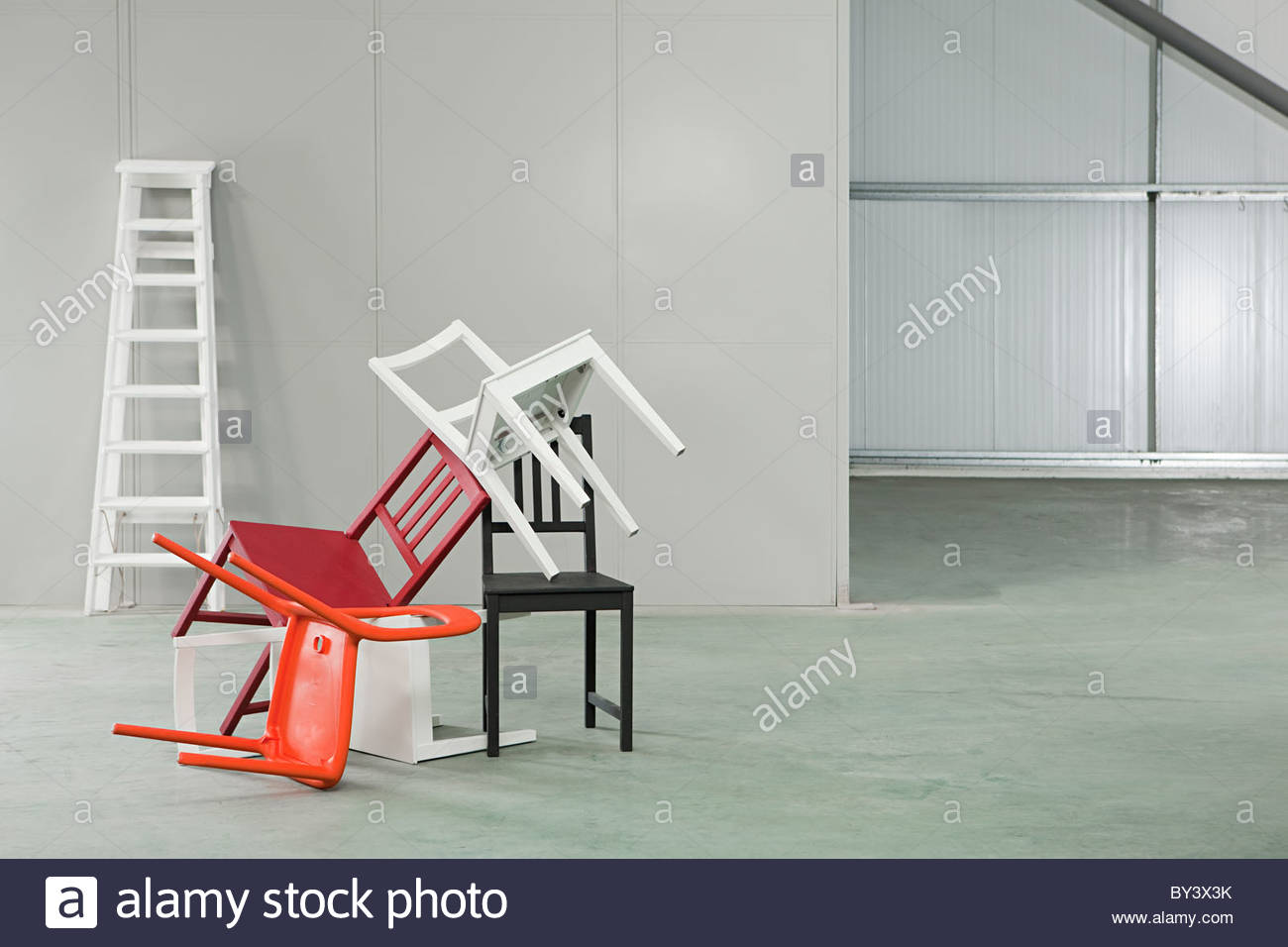 Five chairs piled on top of each other Stock Photo