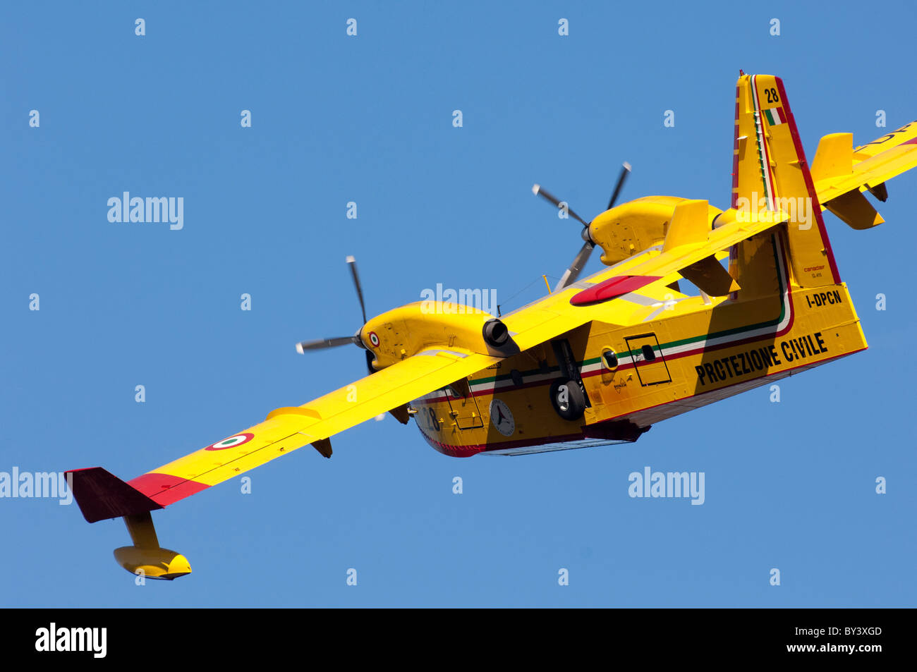 A fire fighting water bomber practices over lake Coghinas in northern Sardinia. - Stock Image