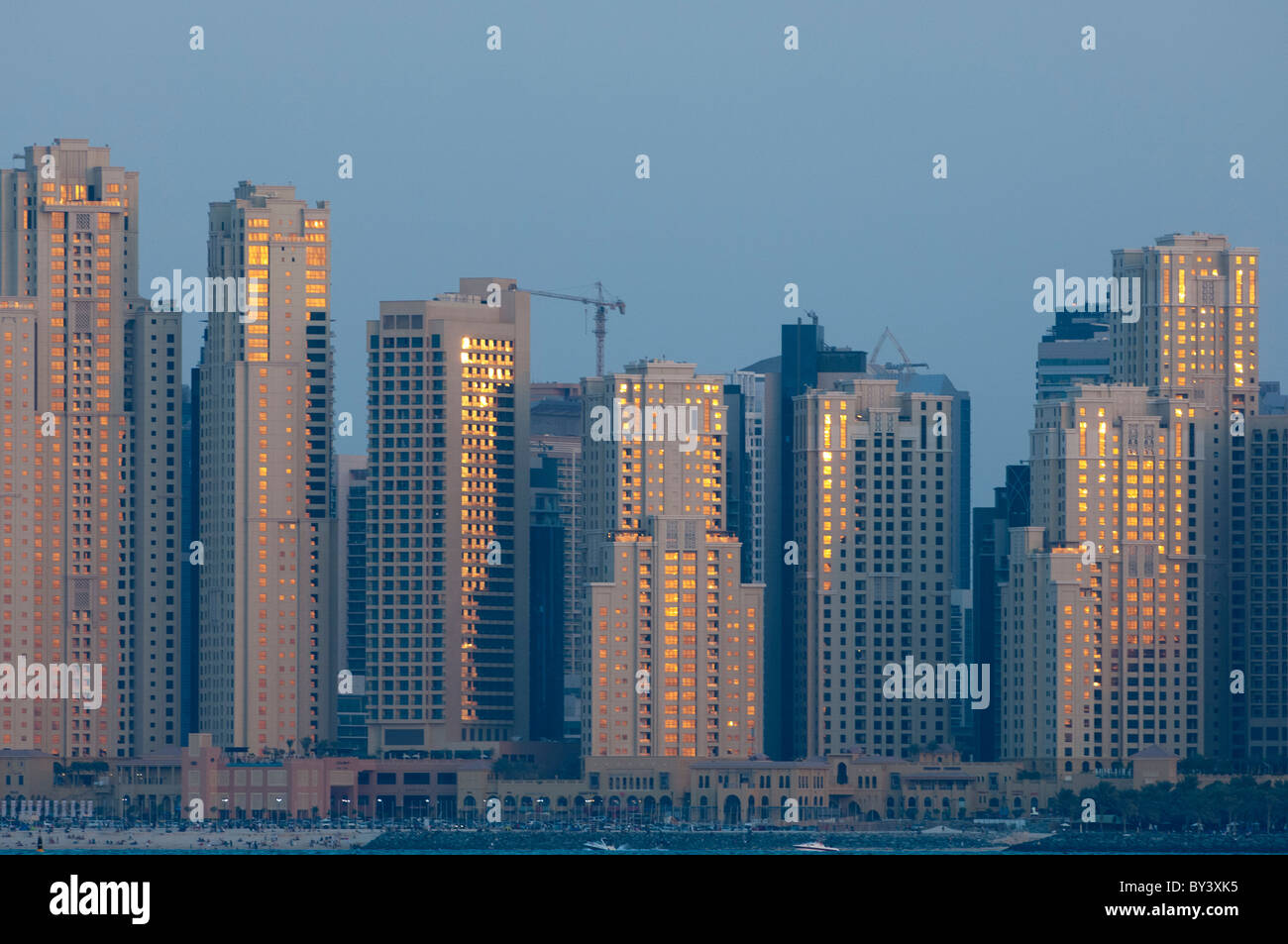 Sunset reflects of high rise buildings on Dubai's waterfront. - Stock Image