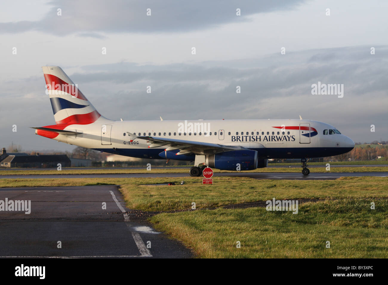 British Airways A319, G-EUOG,  taxying past at Glasgow Airport - Stock Image